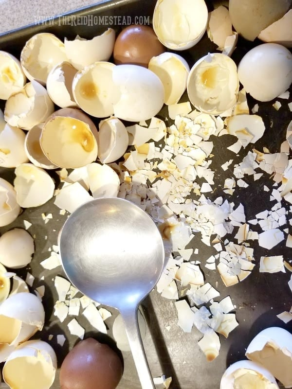 eggshells on baking sheet being smashed with a large spoon for use in the garden