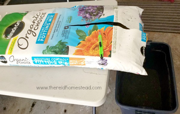pouring large bag of potting soil into a plastic bin