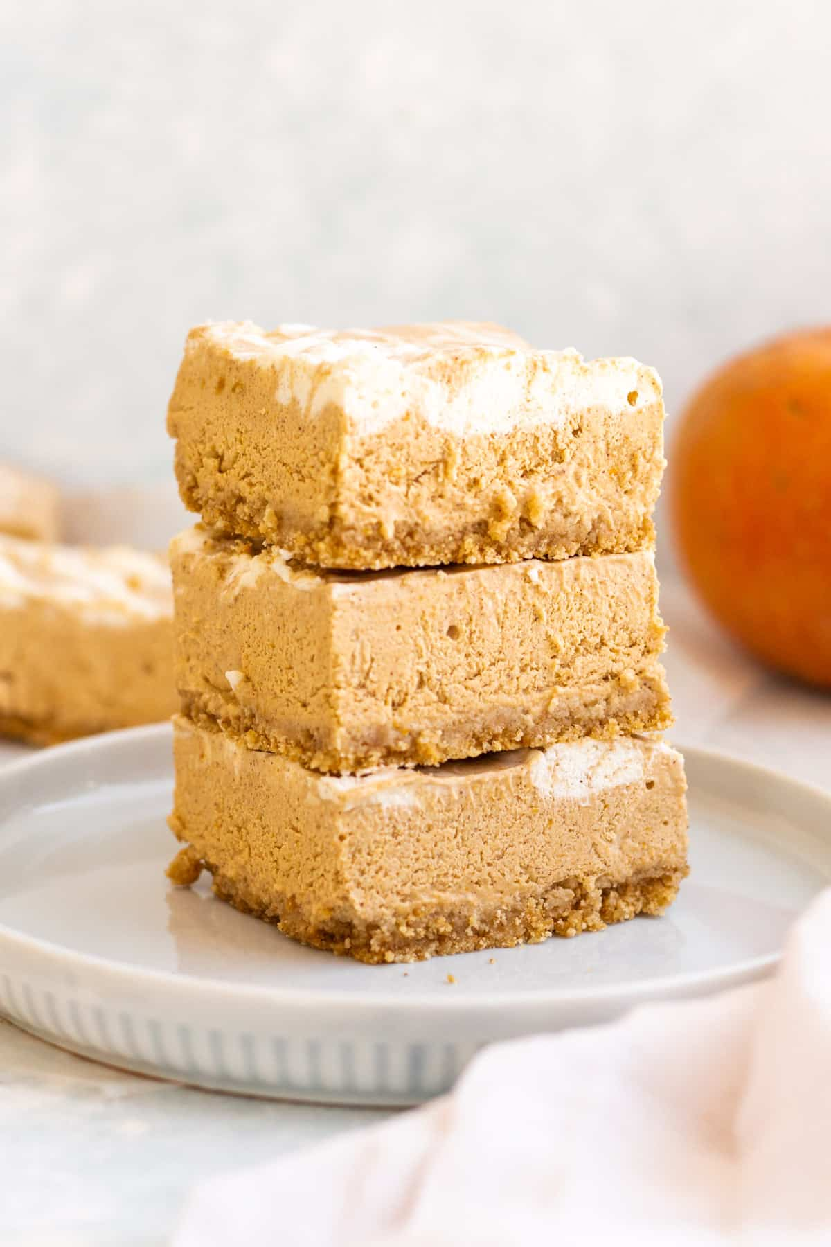 a plate with a stack of no bake pumpkin cheesecake bars