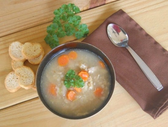 bowl of chicken orzo soup with toast crackers parsley spoon and napkin