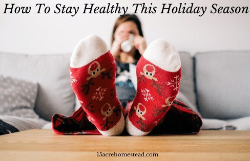 feet with red and white christmas socks on coffee table with person beyond sitting on couch drinking from a mug with text overlay how to stay healthy this holiday season