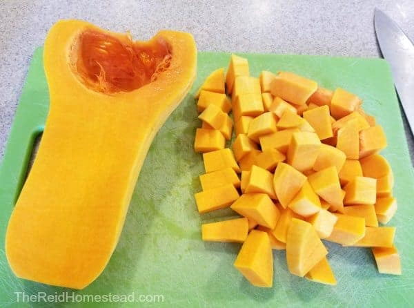 half a butternut squash and a pile of cubed butternut winter squash on a green cutting board