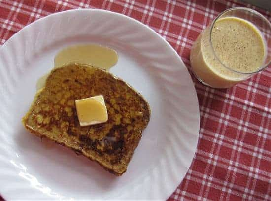 french toast with butter syrup on white plate on red and white tablecloth with a glass of eggnog