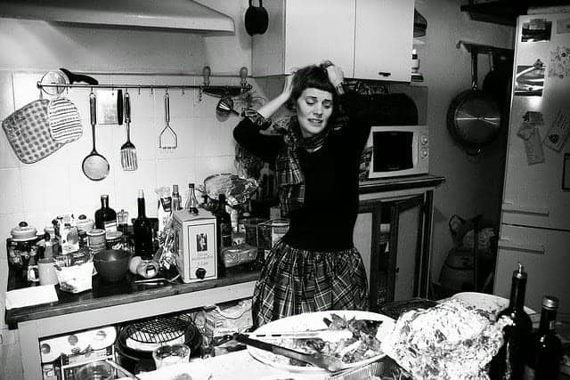 black and white vintage photo of women thowing her hands up in a dirty kitchen