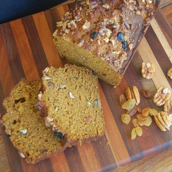 pumpkin bread slices on cutting board with dried fruit and pecans