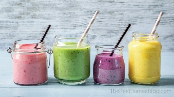 4 different smoothies with straws, a pink one a green one a purple one and a yellow one