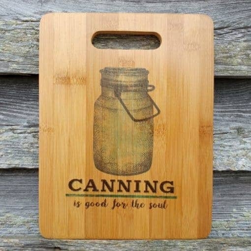 """close up of cutting board with mason jar design on it with the words """"canning is good for the soul"""""""