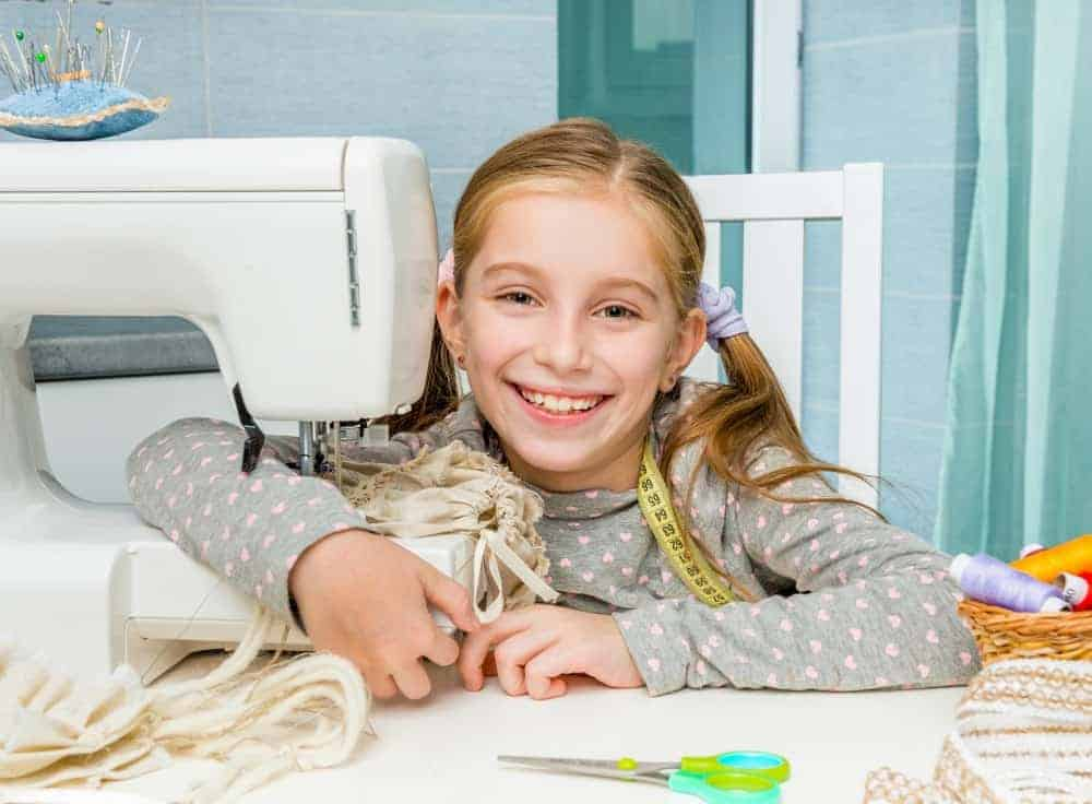 young girl smiling while working at sewing machine