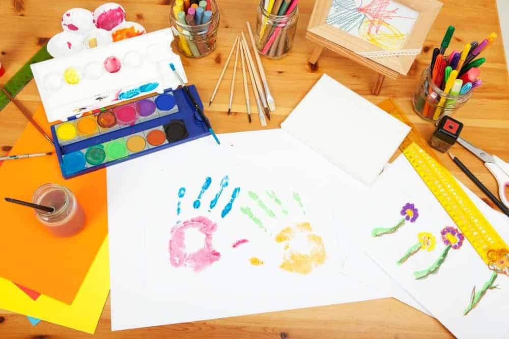 table full of arts and crafts with childs hands printed in paint on papers