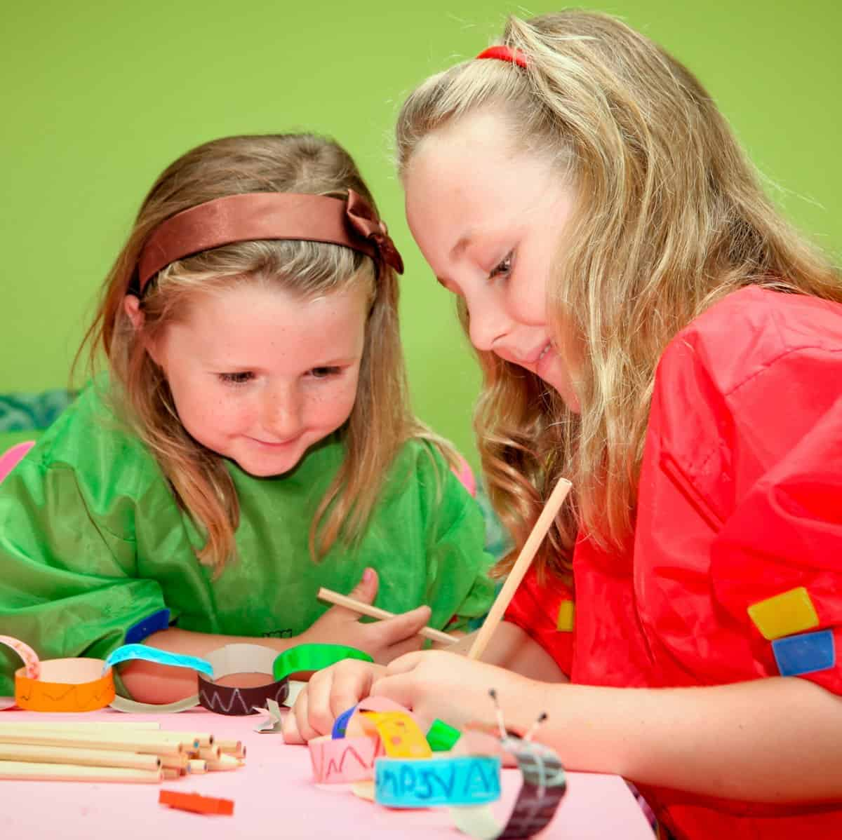 2 little girls with smocks on doing arts and crafts at the table
