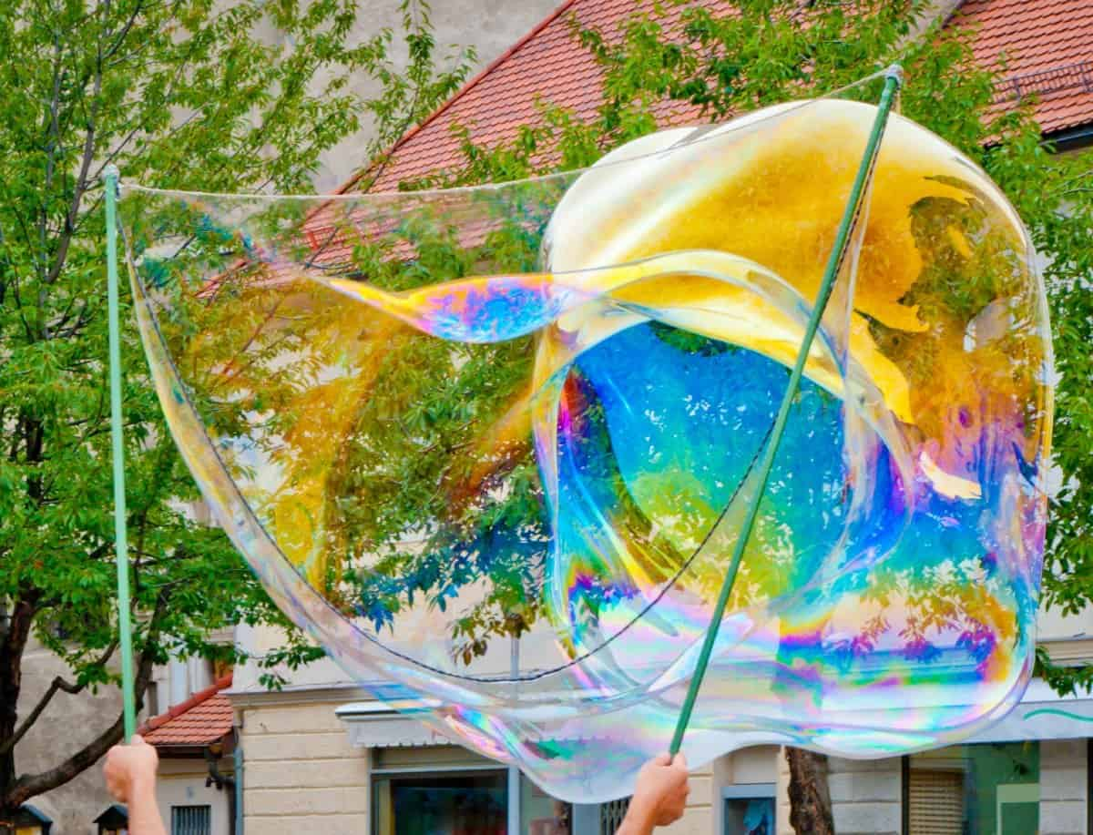 a really large bubble with colorful reflections created using 2 sticks with strings between them