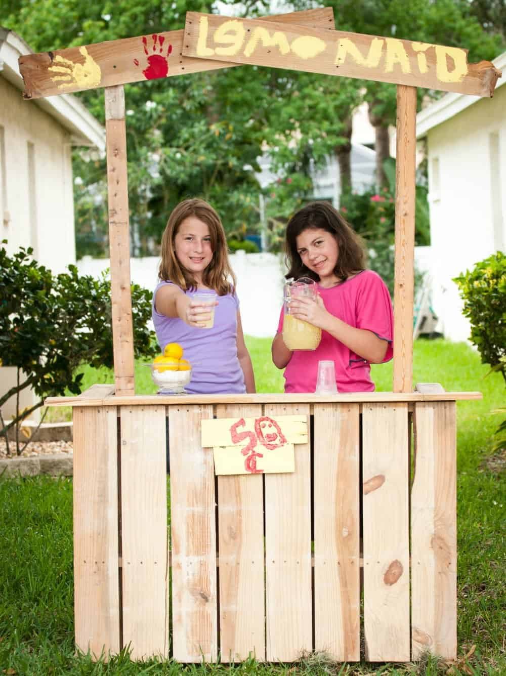 2 girls selling lemonade at their home made lemonade stand