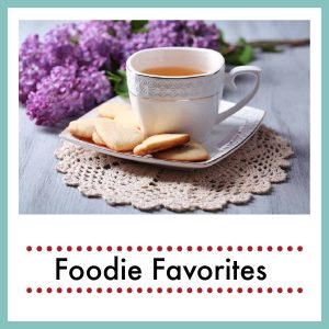 a cup of tea with cookies and a a branch of lilac with text overlay foodie favorites