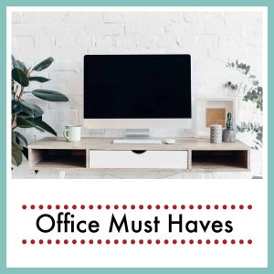 a desk top with large monitor and plants on it with text overlay Office Must Haves