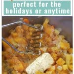 a pot full of chopped and boiled root vegetables and butternut squash with a stick of butter and a potato masher, with text overlay Root Veggie Mash with Butternut Squash Recipe