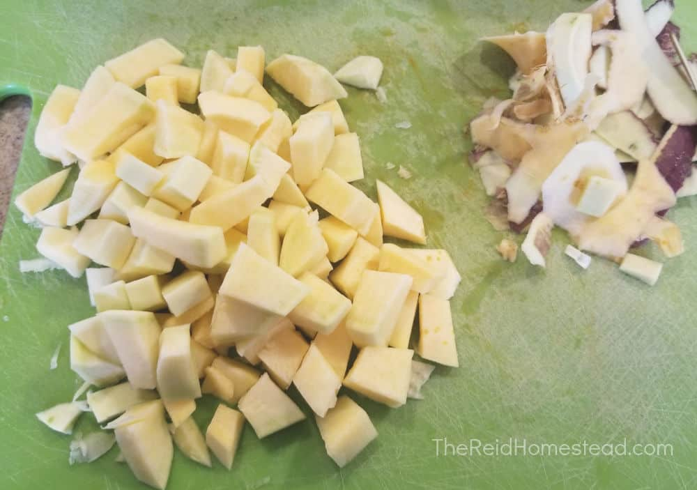 chopped rutabaga on cutting board with peeled rutabaga skins next to them