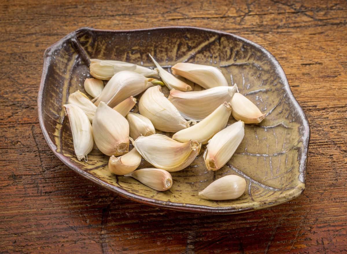 leaf shaped bowl full of garlic cloves